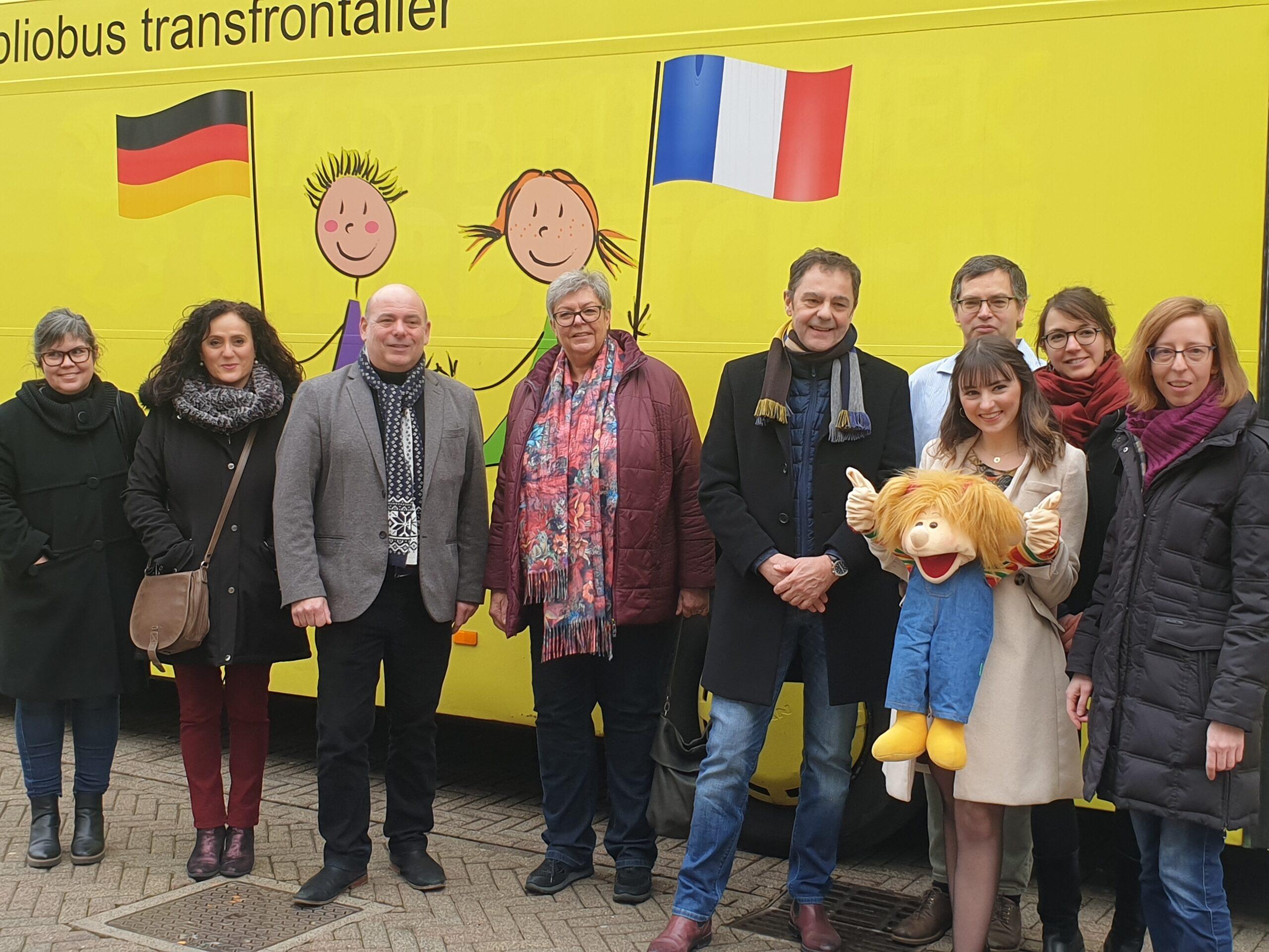 Menschen vor Bus mit deutscher und französicher Flagge