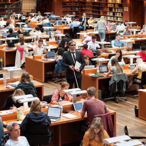Mann mit Blindenstock geht durch Lesesaal der SLUB Dresden