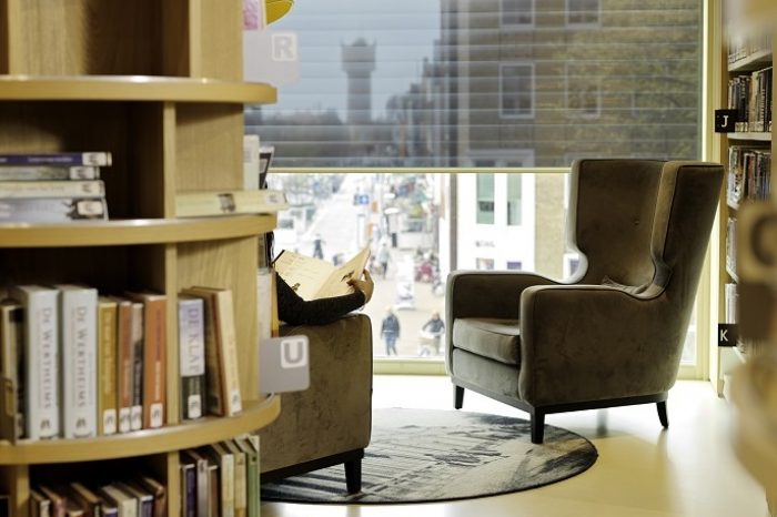 Vrouw leest boek, uitzicht op de stad. School7 bibliotheek Den Helder